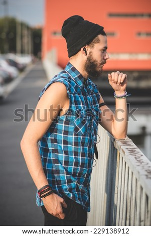 young handsome bearded hipster man using smartphone and listening music with earphones in the city