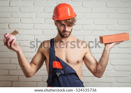 young handsome bearded macho man builder with sexy muscular athletic strong body has strong hands in orange hard hat or helmet holds pig dollar moneybox and brick on white wall background