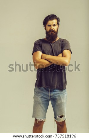 young handsome bearded man or guy with stylish hair and long beard with moustache on serious face in fashion jeans shorts and shirt in studio on grey background, copy space