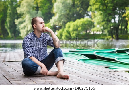 Young handsome bearded man sitting on wooden pier in summer day, relaxing and thinking - stock photo