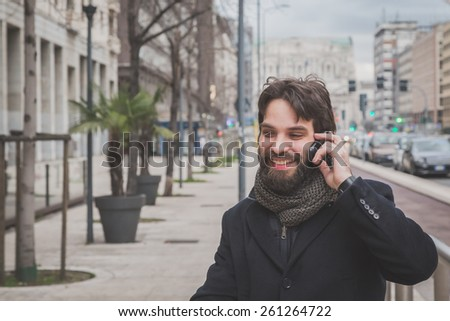 Young handsome bearded man with coat talking on phone in the city streets