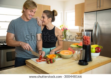 Young handsome beauty couple lovers dating make smoothie slicing fresh fruits and veggies - stock photo