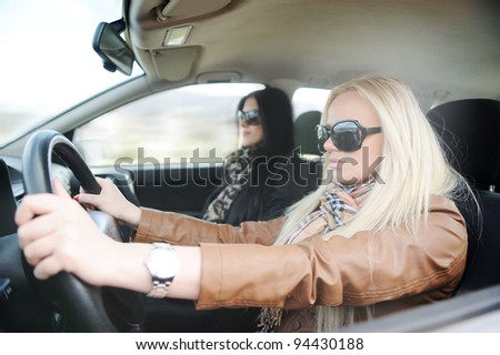 Young handsome blonde female and her girlfriend in a car - stock photo
