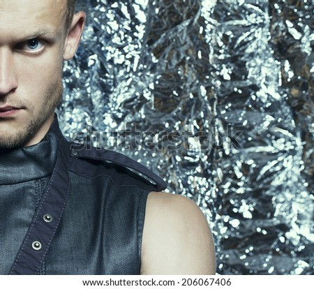 Young handsome blue-eyed man with strong intense look in sleeveless zip-front vest of dark jeans posing over silver foil background. Half-length portrait. Close-up. Studio shot - stock photo