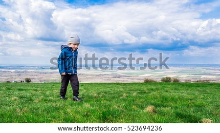 young handsome boy walking on green grass and enjoying his stay on fresh air