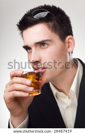 young handsome business man drinking whiskey close up - stock photo