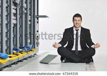 young handsome business man in black suit and tie practice yoga and relax at network server room while representing stres control concept - stock photo
