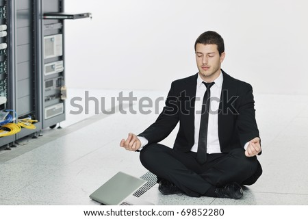 young handsome business man in black suit practice yoga and relax at network server room while representing stress control concept