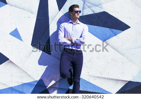 Young handsome business  man in blue  suit and glasses watching against painted wall - stock photo