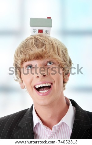 Young handsome business man with house model on head- real estate - stock photo