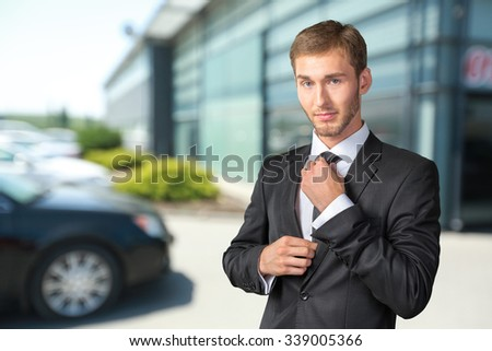 Young handsome businessman adjusting his tie