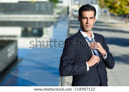 Young handsome businessman, dressed in blue suit, adjusting a tie in urban background with modern office buildings. Caucasian man with blue eyes.