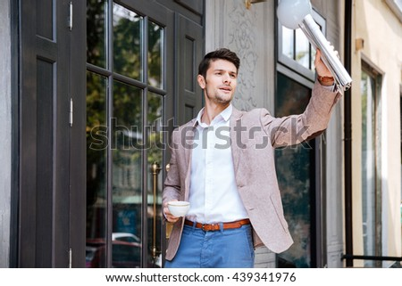 Young handsome businessman greeting someone at coffee shop outdoors