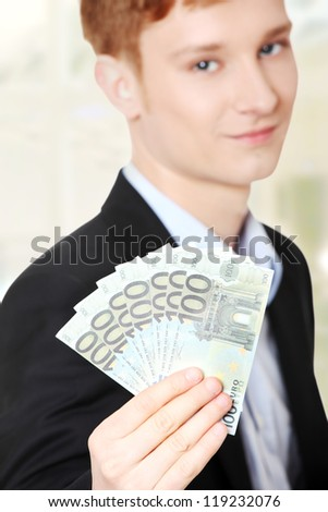 Young handsome businessman holding euros money. - stock photo