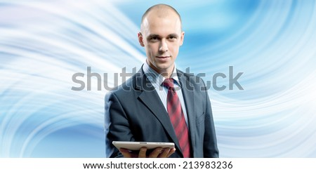 Young handsome businessman holding tablet pc in hand