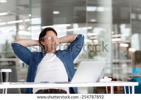 Young handsome businessman in an office having a break - stock photo