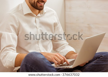 Young handsome businessman in white classical shirt and jeans using a laptop, while working, close-up - stock photo