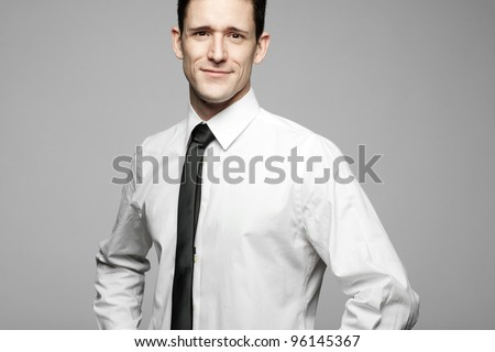 Young handsome businessman in white shirt on gray background. - stock photo