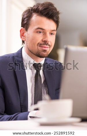 Young handsome businessman is working on laptop. - stock photo