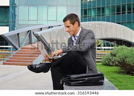 Young handsome businessman, manager using laptop outdoors, in the city, in front of modern building.