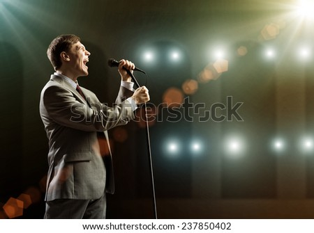 Young handsome businessman sining on stage in microphone - stock photo
