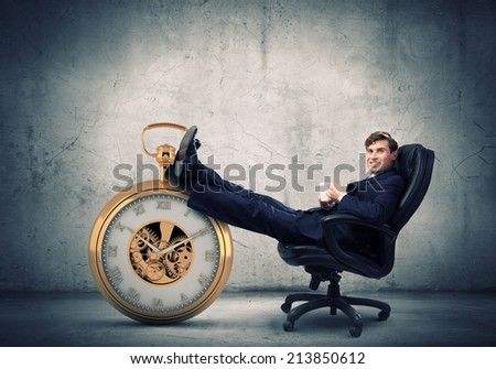 Young handsome businessman sitting in chair with cup - stock photo