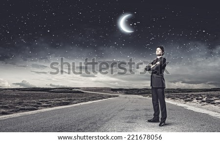 Young handsome businessman standing on asphalt road - stock photo