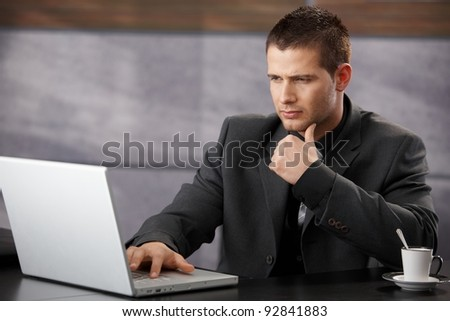 Young handsome businessman using laptop in elegant office.? - stock photo