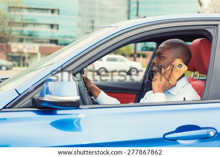 Young handsome businessman using mobile phone while driving car to work. Risky, reckless driver bad habits. Traffic safety rule violation lack of attention concept - stock photo