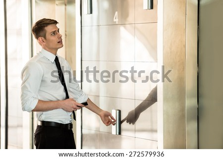 Young handsome businessman waiting on elevator of an business center. - stock photo