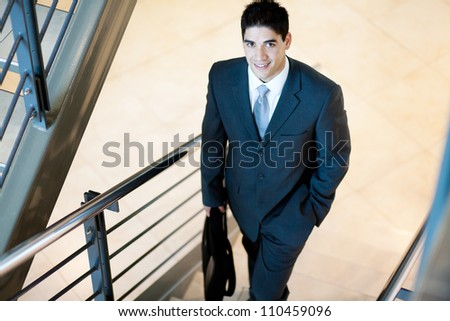 young handsome businessman walking up stairs - stock photo