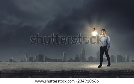 Young handsome businessman walking with lantern in darkness