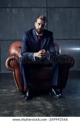 Young handsome businessman with beard in black suit sitting on chair and looking on camera.