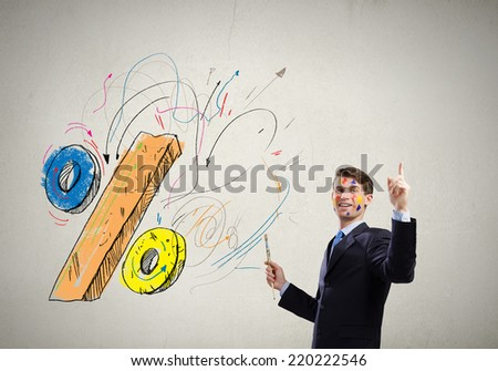Young handsome businessman with brush in hand - stock photo