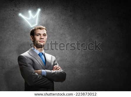Young handsome businessman with crown above his head - stock photo