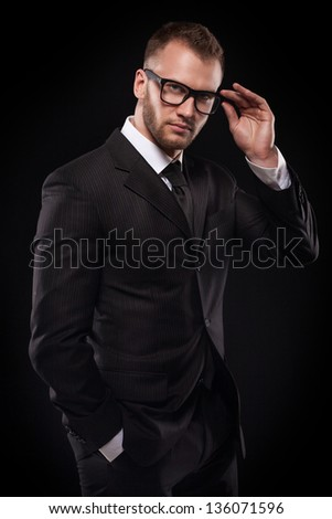 Young handsome businessmanman in black suit and glasses isolated on black background - stock photo