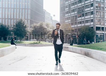 Young handsome caucasian black hair modern businessman walking in the city, smartphone handhold, looking down and tapping touchscreen - working, business, successful concept - stock photo