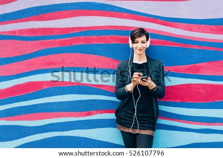 Young handsome caucasian brown hair woman leaning against a wall, listening music with headphones and smart phone hand hold - serene, enjoying, music concept