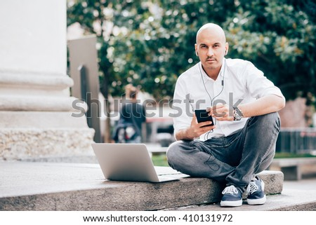 Young handsome caucasian businessman looking in camera with smart phone hand hold, listening music with earphones and computer leaning next to him - multitasking, business, technology concept - stock photo