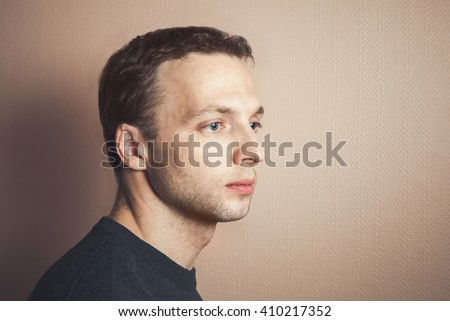 Young handsome Caucasian man closeup profile portrait over gray wall background, vintage tonal correction photo filter effect - stock photo