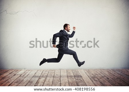 Young handsome Caucasian man in formal wear running and jumping with happy smile - stock photo