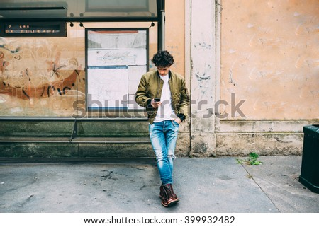 Young handsome caucasian man leaning on a bus stop holding a smart phone looking down and tapping the screen - technology, social network, communication concept - stock photo