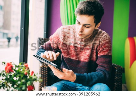 Young handsome caucasian man sitting in a bar, holding a tablet, looking down and tapping the screen - social network, technology, communication concept - stock photo