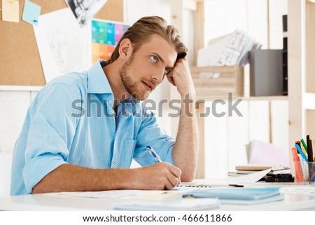 Young handsome confident pensive businessman working sitting at table thinking over notepad. White modern office interior background.