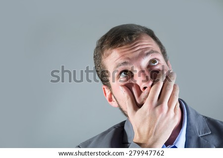 Young handsome desperate man, covering his mouth with unbelieving gesture - stock photo