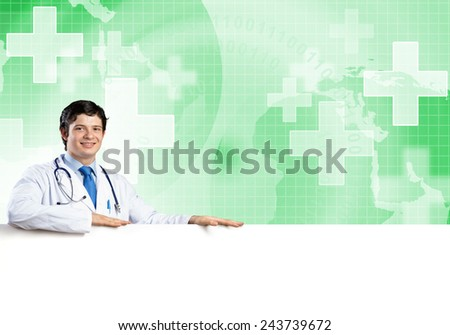 Young handsome doctor holding white blank banner. Place your text - stock photo