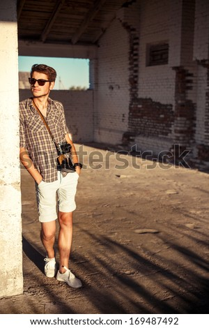 Young handsome fashion man posing outdoor in summer smiling and having fun alone in morning - stock photo