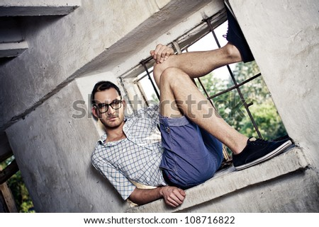 young handsome fashion model man lie in window - colorized photo - stock photo