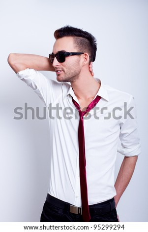 young handsome fashion model man posing in white shirt with red tie - stock photo
