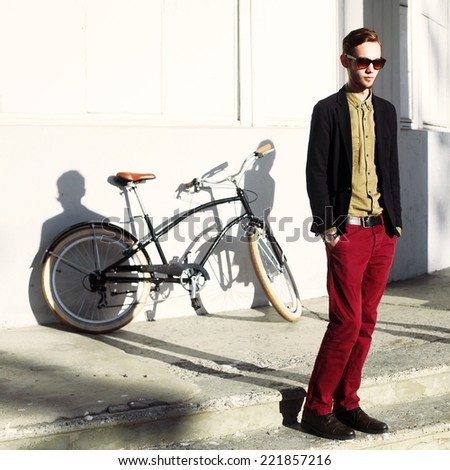 Young handsome fashion serious hipster man posing outdoor with retro bicycle   - stock photo